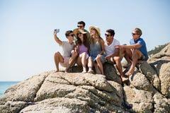 Amis prenant le selfie tout en se reposant sur des formations de roche Photos stock