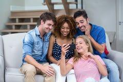 Amis prenant le selfie tout en se reposant sur le sofa Photos libres de droits
