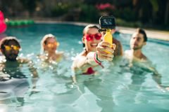 Amis prenant le selfie à la réception au bord de la piscine Photo stock