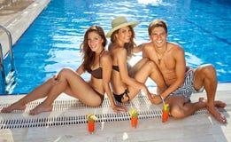 Amis prenant un bain de soleil au bord d'une piscine Image stock