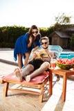 Amis prenant un bain de soleil, livre de lecture, se trouvant près de la piscine Photographie stock libre de droits