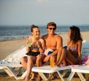 Amis prenant un bain de soleil sur des chaises de plate-forme sur une plage Photos libres de droits
