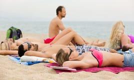 Amis prenant un bain de soleil sur la plage Image stock