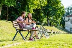 Amis prenant un repos de faire du vélo en parc Image libre de droits