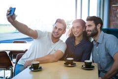 Amis prenant un selfie dans le café Images libres de droits
