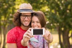 Amis prenant un selfie en parc Image stock