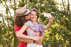 Amis prenant un selfie en parc Images stock