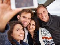 Amis prenant un selfie tandis que sur une promenade en voiture ensemble Photographie stock libre de droits