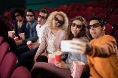 Amis prenant un selfie tout en observant le film Image stock