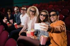 Amis prenant un selfie tout en observant le film Image libre de droits
