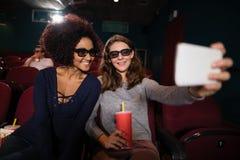Amis prenant un selfie tout en observant le film Photographie stock