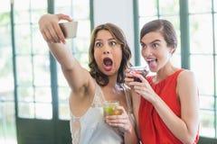 Amis prenant un selfie tout en tenant des verres de cocktail Photo stock