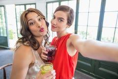 Amis prenant un selfie tout en tenant des verres de cocktail Photos libres de droits