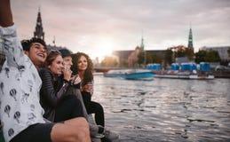 Amis profitant d'un agréable moment par le canal dans la ville Image libre de droits