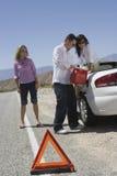 Amis réapprovisionnant en combustible la voiture avec la triangle d'avertissement dans le premier plan Image libre de droits