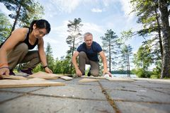 Amis résolvant le puzzle avec les planches en bois sur le patio Photographie stock libre de droits
