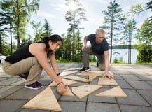Amis résolvant le puzzle en bois de planches sur le patio Image libre de droits