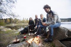 Amis rôtissant des guimauves au-dessus de feu de camp à au bord du lac Photos stock
