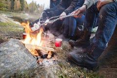 Amis rôtissant des guimauves au-dessus de feu de camp à au bord du lac Photo libre de droits