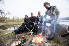 Amis rôtissant des guimauves au-dessus de feu de camp sur au bord du lac Photographie stock libre de droits