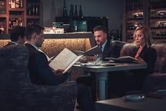 Amis rading le menu dans un restaurant Image stock