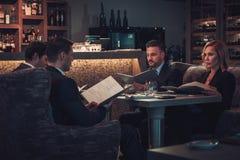 Amis rading le menu dans un restaurant Photos libres de droits