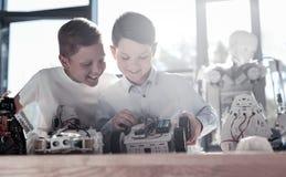 Amis rayonnants construisant l'individu conduisant les machines robotiques dans l'atelier Photos libres de droits