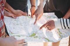 Amis recherchant l'emplacement sur la carte, voyage de rabotage photos stock