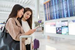 Amis recherchant le numéro de vol dans l'aéroport Photo stock