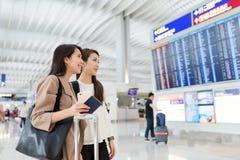 Amis recherchant le numéro de vol en aéroport de Hong Kong Photo stock