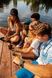 Amis refroidissant ayant l'amusement près du lac Photos stock