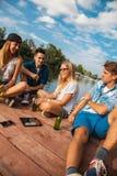 Amis refroidissant ayant l'amusement près du lac Images libres de droits