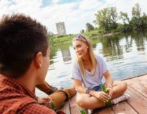 Amis refroidissant près du lac Photos libres de droits