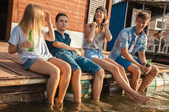 Amis refroidissant près du lac Images libres de droits