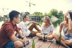 Amis refroidissant près du lac Photos stock