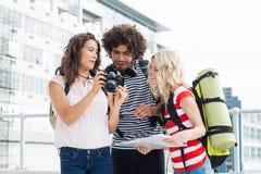 Amis regardant dans l'appareil-photo sur la terrasse Photo libre de droits
