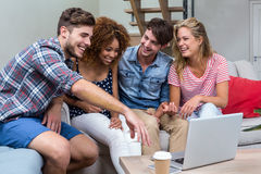 Amis regardant dans l'ordinateur portable tout en se reposant sur le sofa Images stock