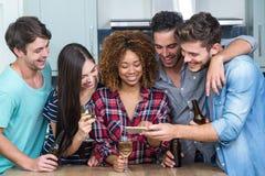 Amis regardant dans le téléphone portable tout en se tenant prêt la table Photo stock