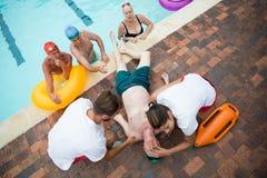 Amis regardant des maître nageurs enregistrant l'homme supérieur inconscient au poolside Images libres de droits