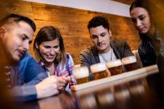 Amis regardant des verres de bière dans le restaurant Photos stock