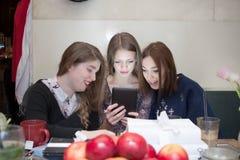 Amis regardant l'affichage de comprimé dans le café Photo libre de droits