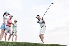 Amis regardant l'homme jouant le golf contre le ciel Photos libres de droits