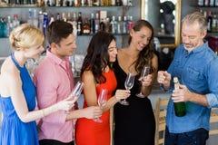 Amis regardant l'homme pour ouvrir la bouteille de champagne Photo libre de droits