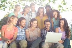 Amis regardant l'ordinateur portable en parc Image libre de droits