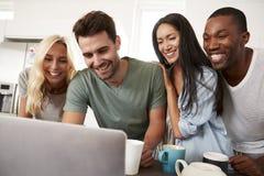 Amis regardant l'ordinateur portable et buvant du café dans la cuisine moderne Image libre de droits