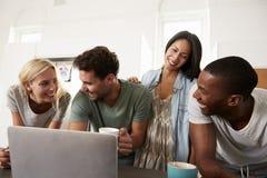 Amis regardant l'ordinateur portable et buvant du café dans la cuisine moderne Images libres de droits