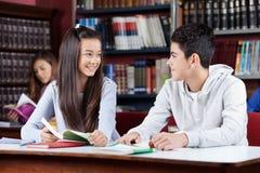 Amis regardant l'un l'autre le Tableau dans la bibliothèque Image libre de droits