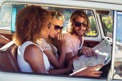 Amis regardant la carte dans campervan Photos stock