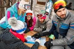 Amis regardant la carte dans la neige un jour froid d'hiver Image libre de droits