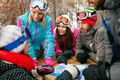 Amis regardant la carte et parlant dans la neige un hiver froid Images stock